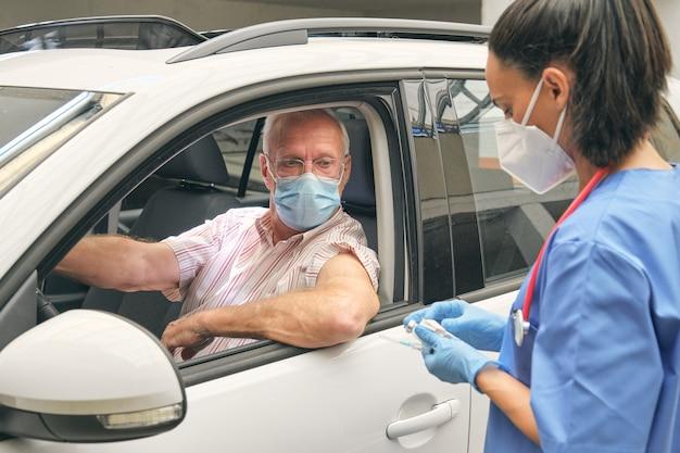 Enfermeira da plantação com vacina contra motorista no carro