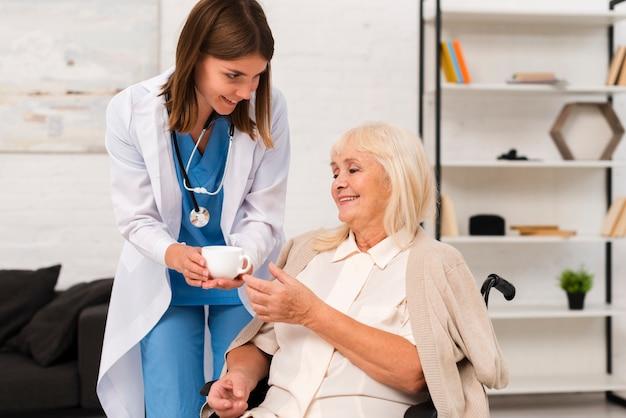Enfermeira dando chá para a velha