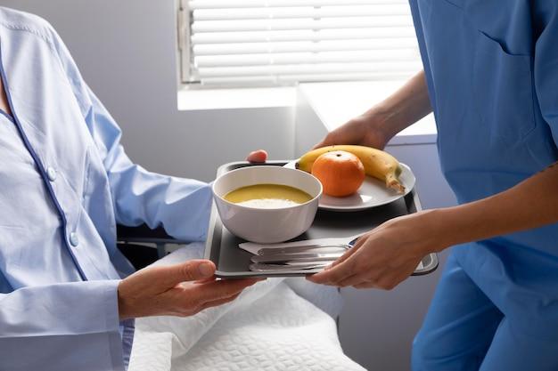 Enfermeira dando comida a um paciente