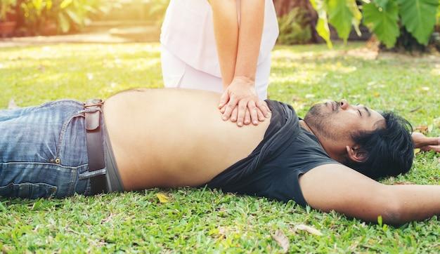 Enfermeira dando reanimação cardiopulmonar para homem em parque de grama