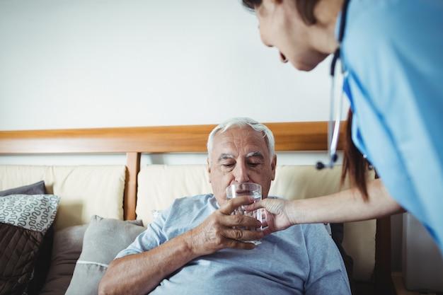Enfermeira dando um copo de água para homem sênior