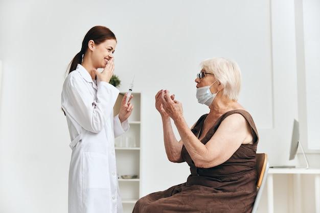 Enfermeira dando uma injeção em uma mulher idosa, passaporte de vacina de vacinação