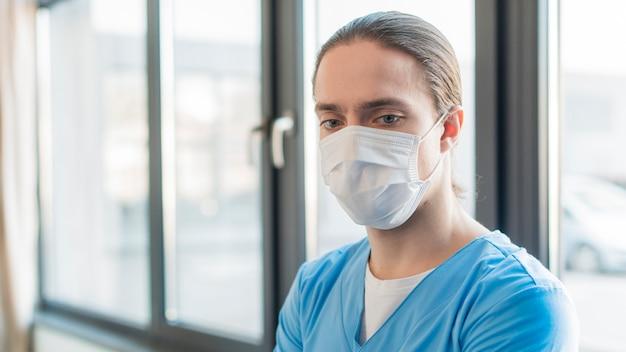 Enfermeira de alto ângulo masculino com máscara médica