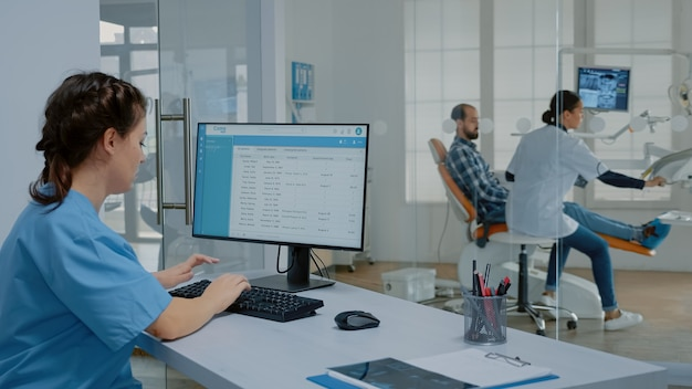 Enfermeira de estomatologia sentada na mesa trabalhando no computador