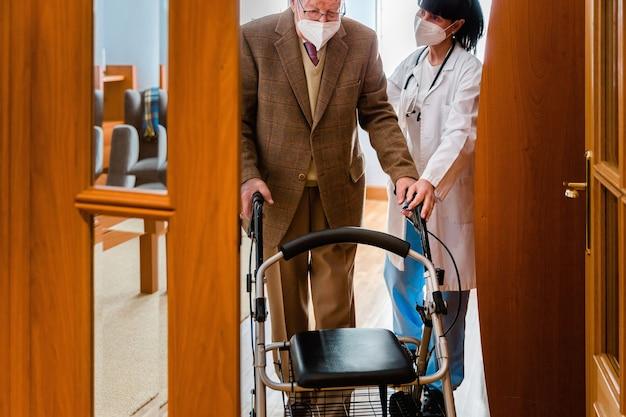 Enfermeira de jaleco branco segurando a mão de um homem idoso com um andador dentro de casa