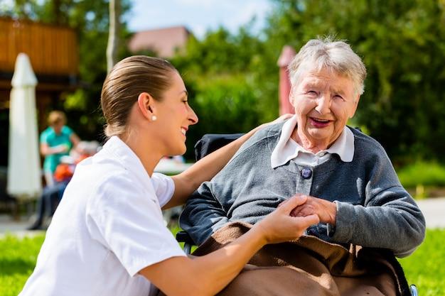 Enfermeira de mãos dadas com mulher idosa em cadeira de rodas