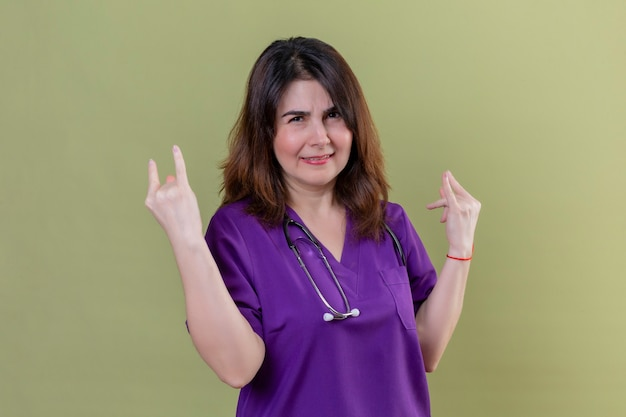 Enfermeira de meia idade usando uniforme e estetoscópio olhando para a câmera sorrindo alegremente fazendo símbolos de rock com as duas mãos em pé sobre um fundo verde