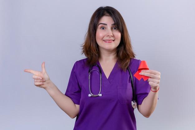 Enfermeira de meia idade vestindo uniforme e com estetoscópio segurando a fita vermelha, um símbolo da luta contra a aids sorrindo