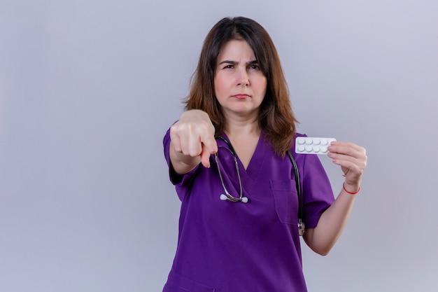 Enfermeira de meia idade vestindo uniforme médico e com estetoscópio segurando a bolha com pílulas apontando descontente