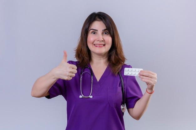 Enfermeira de meia idade vestindo uniforme médico e estetoscópio segurando uma bolha com comprimidos, olhando para a câmera com uma cara de hapy aparecendo polegares em pé sobre um fundo branco
