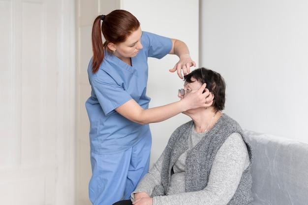Enfermeira de tiro médio ajudando mulher