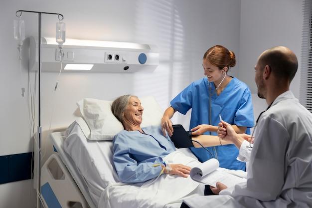 Enfermeira de tiro médio e médico verificando o paciente