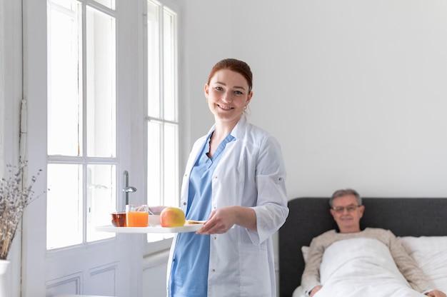 Enfermeira de tiro médio segurando a bandeja