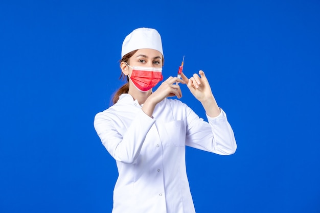 Enfermeira de vista frontal em um terno médico branco com máscara vermelha e injeção em suas mãos em azul