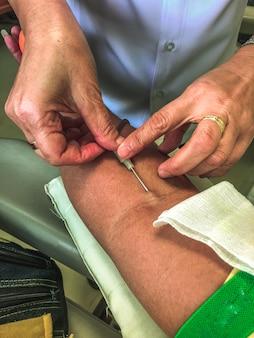 Enfermeira desinfecção do braço masculino antes do exame de sangue.
