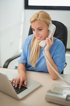 Enfermeira digitando em um laptop enquanto segura um telefone