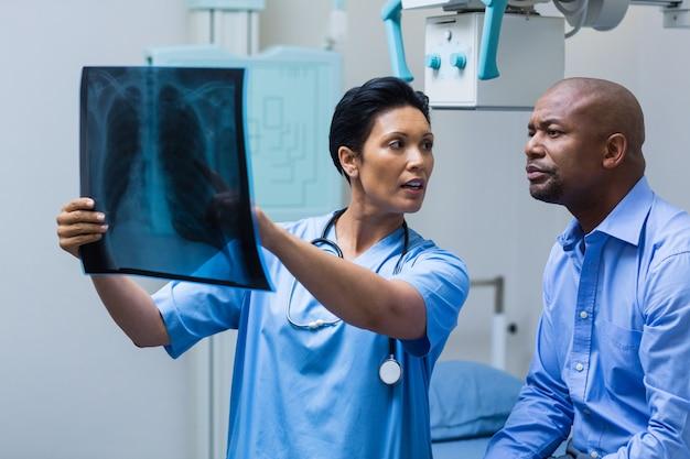Enfermeira, discutindo o raio-x com o paciente