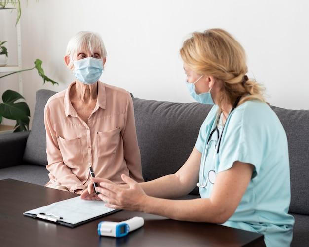 Enfermeira e mulher idosa conversando em uma casa de repouso