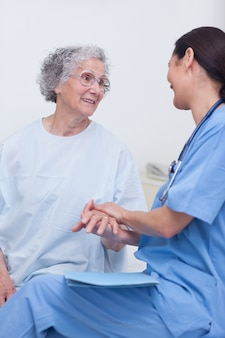 Enfermeira e um paciente sentado em uma cama