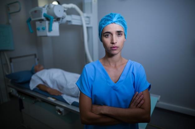 Enfermeira em pé com os braços cruzados na sala de raio-x