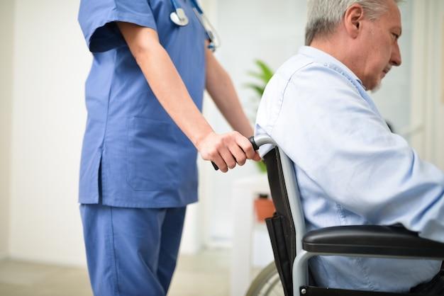 Enfermeira empurrando um paciente em uma cadeira de rodas