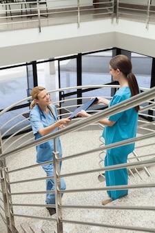 Enfermeira entregando pasta para outra enfermeira