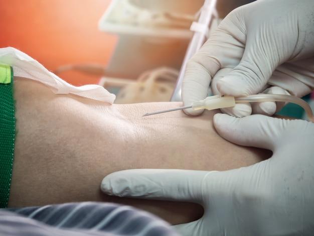 Enfermeira esfaquear agulhas médicas para doar o braço. doador de sangue fazendo doação.
