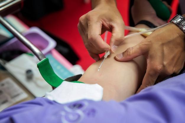Enfermeira esfaquear agulhas médicas para doar o braço.