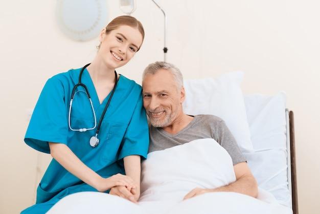 Enfermeira está deitada ao lado de um paciente e olhando para a câmera.
