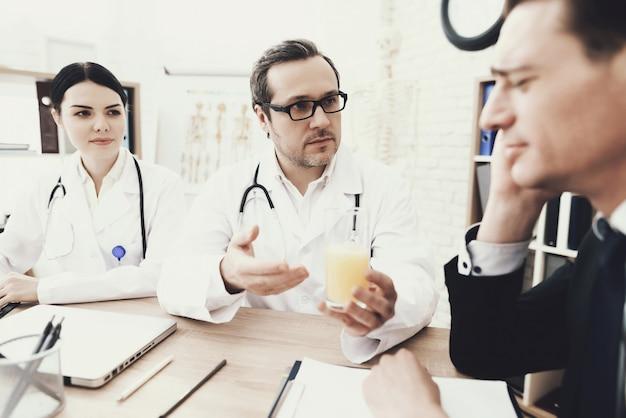 Enfermeira está escrevendo notas. o paciente está sentindo dor de cabeça.