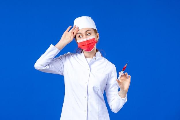 Enfermeira estressada de vista frontal em um terno médico branco com máscara vermelha e injeção em suas mãos no azul