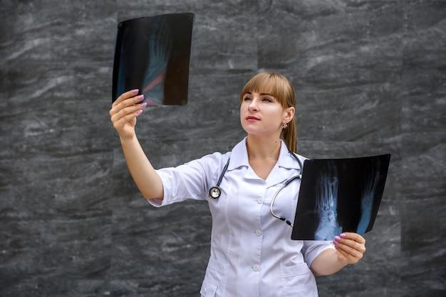 Enfermeira estudante em uniforme médico examina radiografias de fotografias de pés. conceito médico