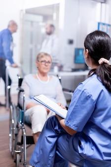 Enfermeira falando com mulher idosa com deficiência em cadeira de rodas sobre sua deficiência