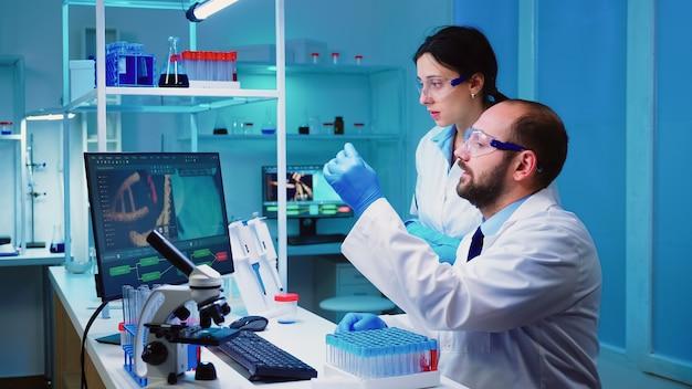 Enfermeira farmacêutica segurando tubos de ensaio levando ao médico conduzindo experimento de dna, discutindo sobre tratamento médico fazendo hora extra