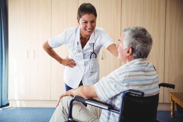 Enfermeira feliz sorrindo para seu paciente