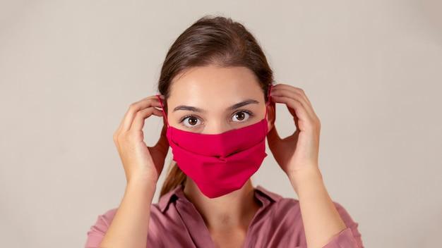 Enfermeira fêmea nova que põe sobre uma máscara médica da tela vermelha durante a pandemia.