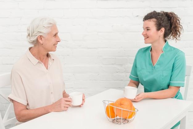 Enfermeira feminina tomando café com mulher sênior, sentado contra a parede branca