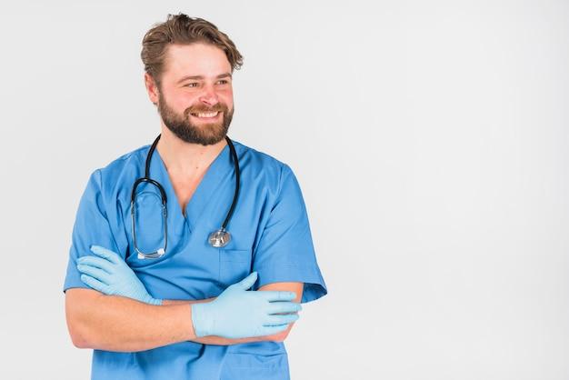 Enfermeira homem cruzando as mãos e desviar o olhar