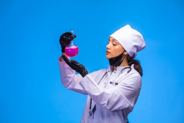 Enfermeira isolada na mão e máscara facial contém frasco químico e olha com atenção.