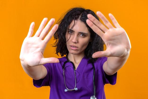 Enfermeira jovem com uniforme médico e estetoscópio em pé com as mãos abertas, fazendo sinal de pare com gesto de defesa de expressão sério e confiante