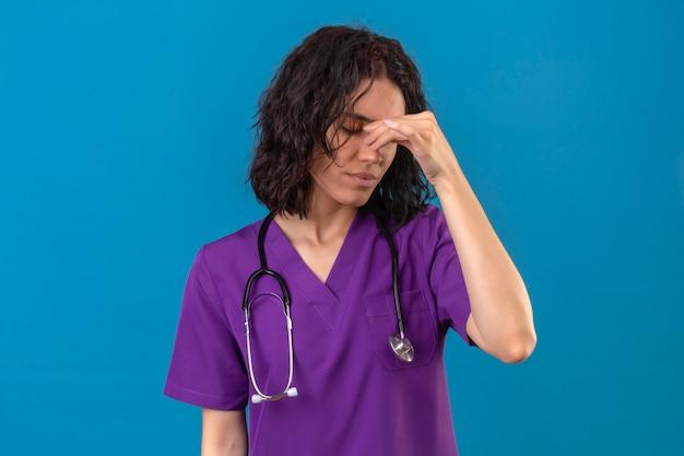 Enfermeira jovem com uniforme médico e estetoscópio tocando o nariz entre os olhos fechados, estressada, sentindo fadiga em pé