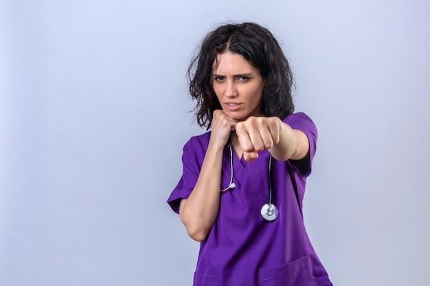 Enfermeira jovem em uniforme médico e com estetoscópio em pé, pronta para lutar com o punho gesto de defesa cara zangada e chateada