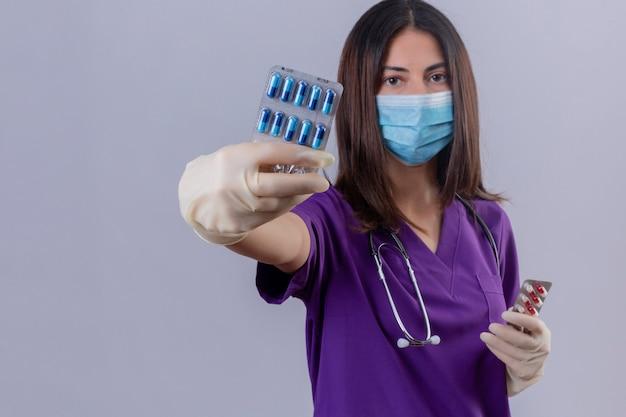 Enfermeira jovem vestindo luvas de máscara protetora de uniforme médico e estetoscópio mostrando bolha com comprimidos, olhando com expressão séria e confiante