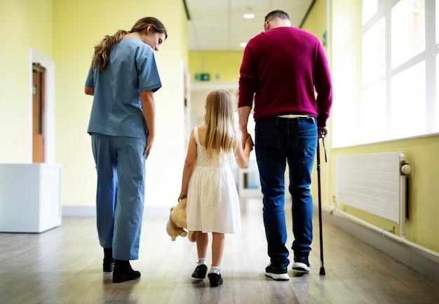 Enfermeira levando um paciente pelo corredor
