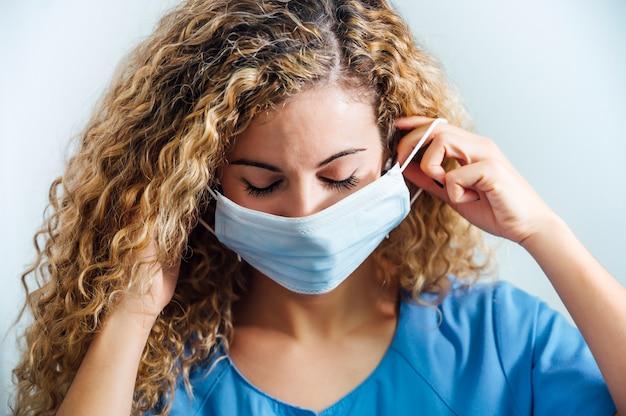 Enfermeira loira ajustando a máscara