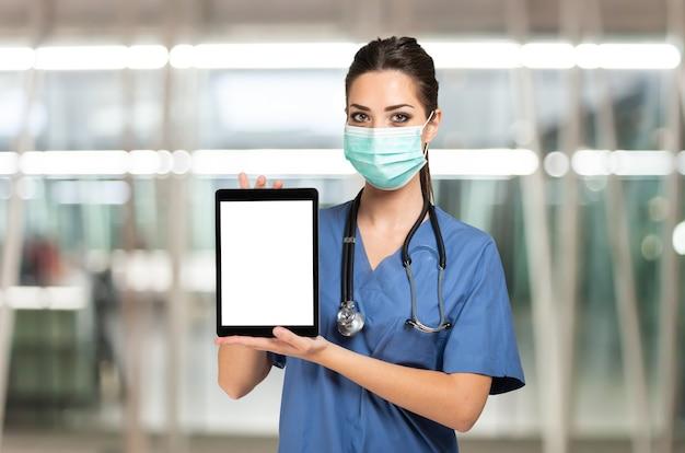 Enfermeira mascarada mostrando um tablet com uma tela branca