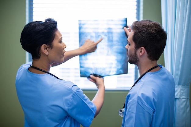 Enfermeira masculina e feminina, discutindo o raio-x na enfermaria
