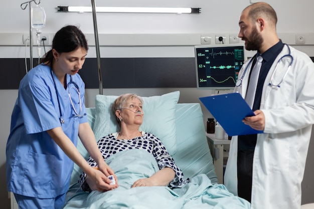 Enfermeira médica anexando oxímetro em paciente idosa