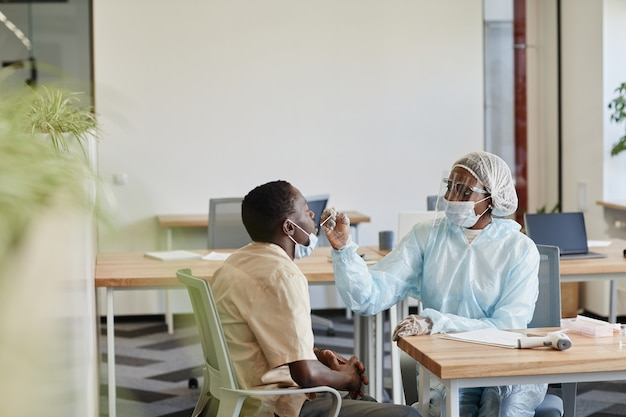 Enfermeira médica em traje de epopéia explicando à paciente como ela obterá amostra para teste de coronavírus