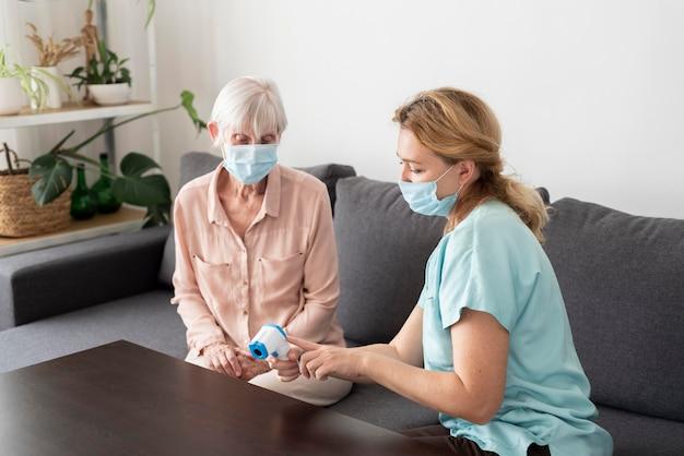 Enfermeira mostrando uma mulher mais velha na casa de saúde o termômetro eletrônico